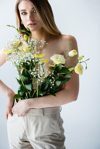 young woman with flowers in pants looking at camera while posing on white