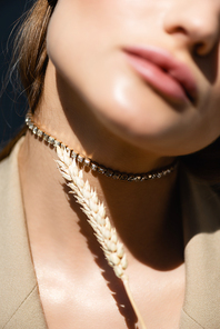 cropped view of woman in necklace near wheat spikelet on dark grey