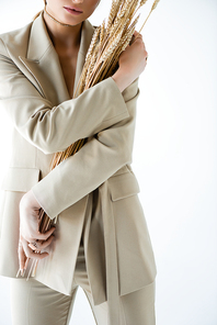 cropped view of young woman in beige blazer holding wheat on white
