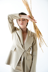 young woman in beige formal wear holding wheat while posing on white