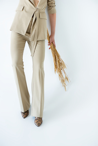 cropped view of young woman in beige pants holding wheat and posing on white