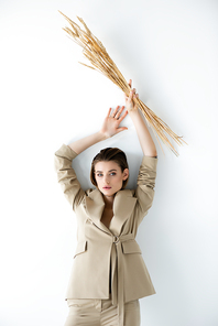 young woman in beige formal wear holding wheat above head on white