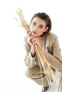 stylish young woman in beige suit sitting while holding wheat on white