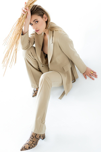young model in beige suit sitting while holding wheat on white