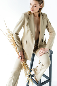 sexy model in suit sitting on stool and holding wheat spikelets on white