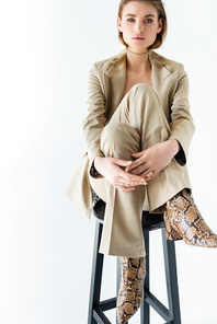 young model in suit poising while sitting on stool on white background