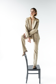 stylish model in beige suit and boots with animal print standing on chair on white
