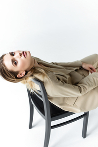 stylish model in beige suit posing on wooden chair on white