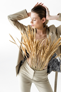 stylish model in beige formal wear with wheat spikelets posing isolated on white