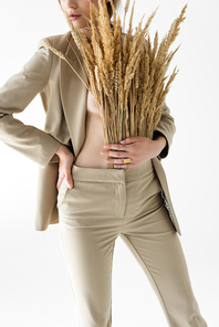 cropped view of sexy model in beige suit with wheat spikelets posing isolated on white