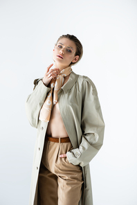 young model in glasses, trench coat and scarf posing isolated on white