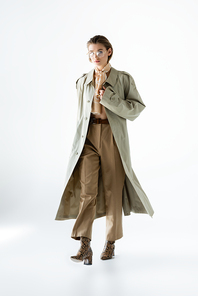 full length of trendy woman in glasses, trench coat and scarf walking on white