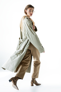 full length of stylish woman in glasses, trench coat and scarf walking on white