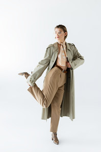 full length of trendy woman in glasses, trench coat and scarf posing on white