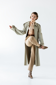 full length of young woman in glasses, trench coat and scarf posing on white