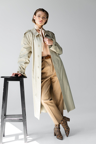 full length of young woman in glasses, trench coat and scarf leaning on stool while posing on grey
