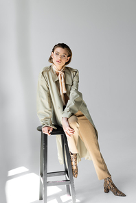 full length of young woman in trench coat and scarf sitting on stool while posing on grey
