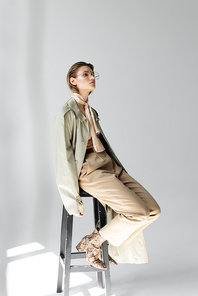 full length of young woman in glasses, trench coat and scarf sitting on stool while posing on grey