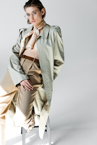 trendy young woman in trench coat and scarf sitting on stool while posing on grey