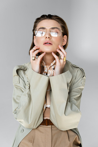 trendy young woman in glasses, trench coat and scarf posing on grey