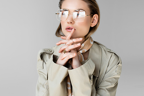 trendy woman in glasses, trench coat and scarf posing on grey