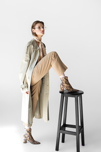 trendy woman in trench coat and scarf posing near chair on white