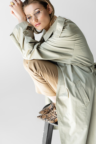 elegant young model in trench coat, glasses and scarf sitting on chair isolated on white