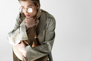 elegant young woman in trench coat, glasses and scarf posing isolated on white