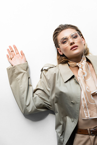 top view of woman in glasses, trench coat and scarf lying on white