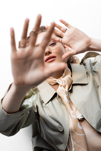 top view of young woman in glasses, trench coat and scarf lying while gesturing on white