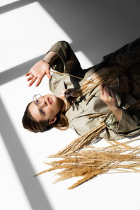 high angle view of model in glasses, trench coat and scarf lying near wheat on white