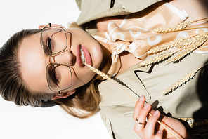 top of model in glasses, trench coat and scarf lying and biting wheat spikelet on white