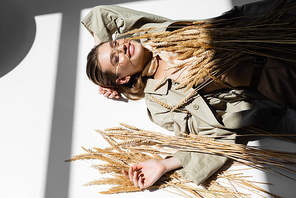 high angle view of cheerful woman in glasses, trench coat and scarf lying near wheat on white