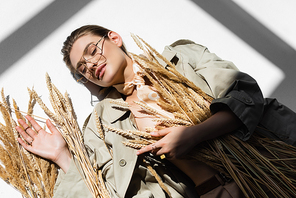 top view of pleased woman in glasses, trench coat and scarf lying near wheat on white