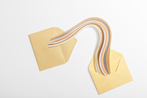 top view of yellow envelopes with multicolored rainbow on grey background