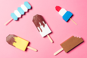 top view of various handmade colorful origami ice cream on pink