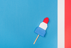 top view of f handmade paper ice cream on blue with stripes and copy space