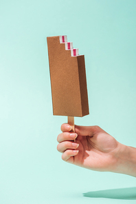 cropped view of young woman holding paper ice cream on turquoise