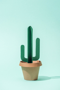 handmade green paper cactus in flower pot on turquoise