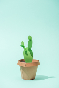 handmade green paper cactus in flower pot on turquoise with copy space
