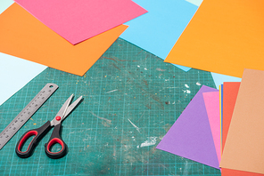 colorful cardboard with scissors and ruler on messy surface