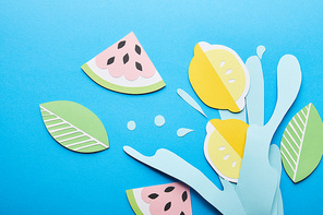 top view of paper cut water splash with lemons, leaves and watermelons on blue background