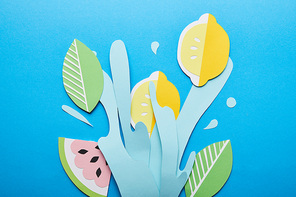 top view of paper cut water splash with lemons, leaves and watermelon on bright blue background