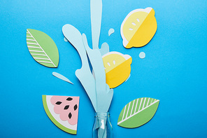 top view of bottle with paper cut water splash, lemons, leaves and watermelon on blue background