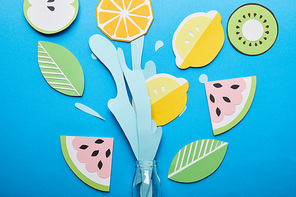 top view of paper cut water splash with fruits near glass bottle on blue background