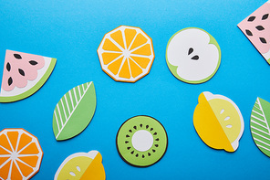 top view of paper cut lemons, leaves, oranges, kiwi and watermelons on blue background