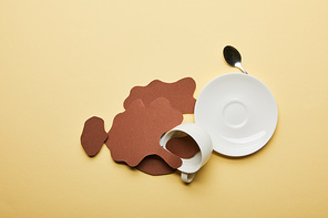 top view of paper cut coffee spills near cup, saucer and spoon on beige background with copy space