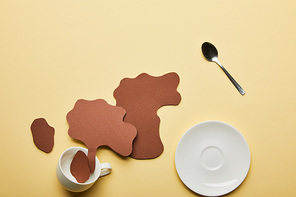 top view of paper cut coffee spills near white cup, saucer and spoon on beige background