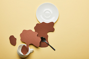 top view of paper cut coffee spills near cup, saucer and spoon on beige background
