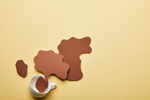 top view of paper cut coffee spills near cup on beige background